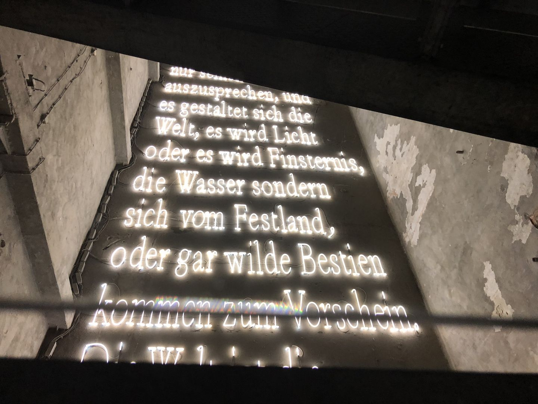 Eine aus Neonröhren geformte Textpassage von Heinrich Heine empfängt die Besucher.