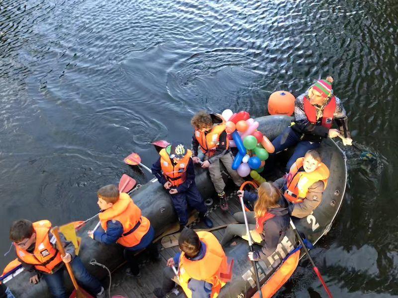 Ein fröhliches Gesicht blickt zum Brückengeländer empor. Mit acht Kindern saßen wir im Boot.