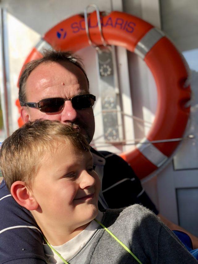 Vater und Sohn genießen die Tour über den See bei goldenem Oktoberwetter.
