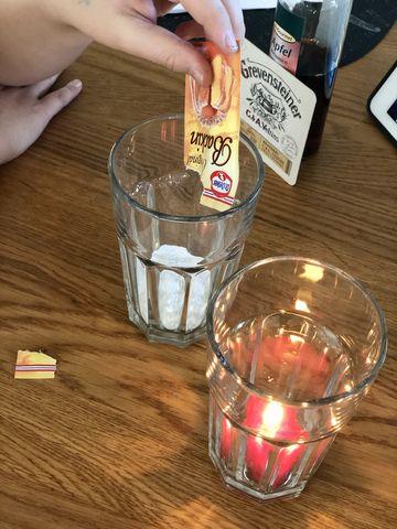 Die Weihnachtsfrau erklärt uns Schritt für Schritt, was zu tun ist: Zunächst zünden wir unser Teelicht an und stellen es in eines der Gläser. In das andere kommt das Backpulver aus dem Tütchen.
