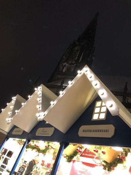 Typisch für den Lambertimarkt sind die blauß-weißen Hütten mit den spitzen Dächern. Darüber ragt der Kirchturm empor.