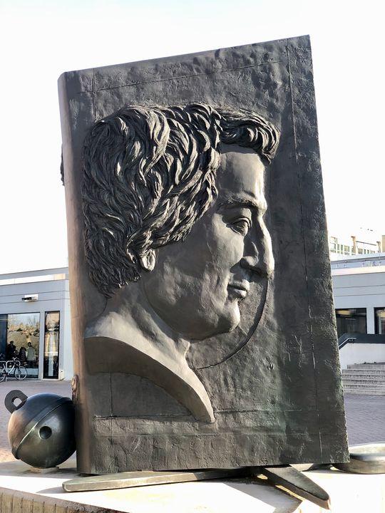 Der Landeswettbewerb findet in der Heinrich-Heine-Universität in Düsseldorf statt. Das vier Meter große Denkmal auf dem Campus zeigt den Dichter als Kämpfer. Der hat allerdings mit Worten gekämpft - ich jetzt mit Zahlen.