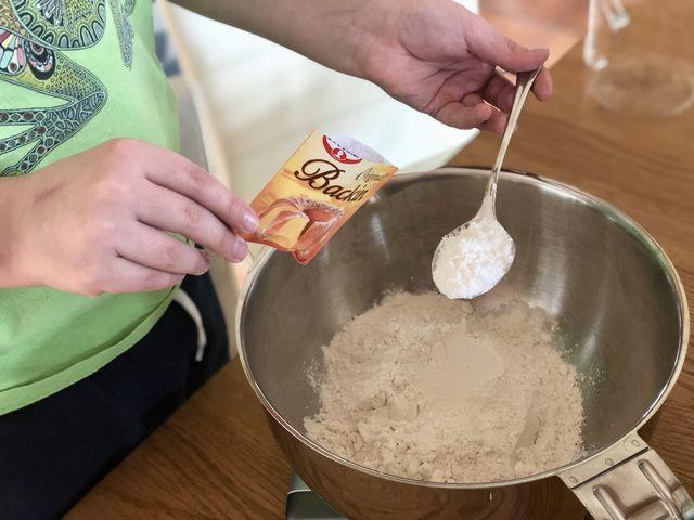 2. Das Mehl mit einem Esslöffel Backpulver und Zucker mischen. Bei normalem Zucker reicht ein Esslöffel. Wir nehmen aber lieber Vanillezucker und - unser Entdecker-Geheimtipp! - einen halben Teelöffel Zimt.