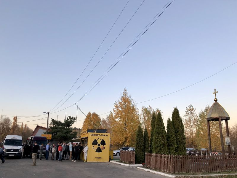 Besuch in Tschernobyl: An der Grenze zur Zone ein seltsames Bild: Neben der Gedenkstätte drängeln sich Touristen am Souvenirstand.