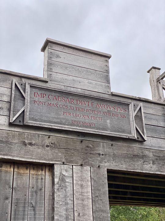 Die Inschrift am Tor verrät so einiges: Kaiser Augustus ließ das Lager durch die 19. Legion bauen - und 2016 wurde es wiedererrichtet.